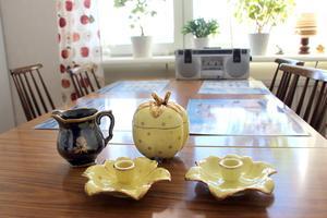 Ljusstakar och äppelskål Neapel i gult och guld och mjölkkanna till en teservis i svart och guld av Arthur Percy.