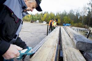 Den här stocken blir lagom. Gösta Jansson mäter upp den stock som ska läggas på det fjärde varvet.