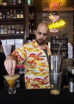Bildtext 09: Ben serverar drinkar på en lokal bar vid Brick Lane.   Foto: Elin Swedenmark