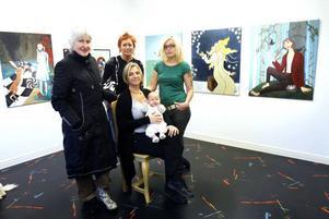 """Sprudlande konstnärer. Iris Santén, Veroniqa Perzon, Johanna Fröjd och Pia de Veen (sittande med bäbis) i sagornas värld – som är temat för årets höstutställning.  På väggen till vänster                       syns Alice i underlandet, till höger """"Snödrottningen""""."""