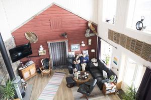För att bevara den timrade ytterväggen på stugan fick de ta till rejält i takhöjd i vardagsrummet.