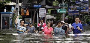 I delar av Bangkok får människor vada genom midjehögt vatten på gatorna.