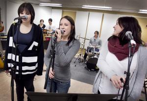 Maja Lindvall, Jenny Melin och Linnea Vonck står vid mikrofonerna när klassen kör Amy Winehouse's svängiga hit Rehab.