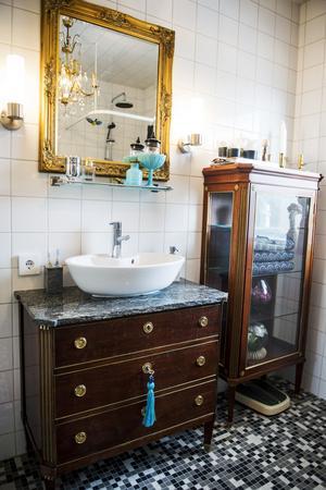Gamla trämöbler bryter av stilen i det nyrenoverade badrummet.