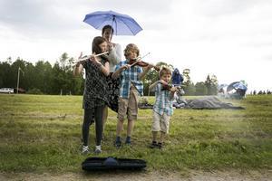 Alma, Arvid och Ingel Lundberg spelas Äppelbo gånglåt. Mamma Sara håller paraplyet.