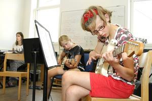 """Madeleine Ferm och Hilma Staffangård lär sig ackord på kollot """"Spela i tjejband"""". I bakgrunden musikhandledaren Carin Hallin under ett tidigare kulturkollo."""
