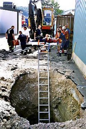 Foto: LEIF JÄDERBERG Mot ambulansen. Åshammarsbon hade klättrat ner i den fyra meter djupa gropen på ABB:s område för att lossa lyftanordningen på en just nedlyft brunnsring. Jord rasade ner på hans rygg när han stod böjd framåt för att skyffla makadam kring betongröret.