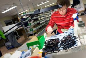 Eva Larsson på Samhall putsar glasen på de bågar som skickas i retur för att de ska vara i fint skick när de sänds till nästa kund för provning.Foto: Håkan Luthman