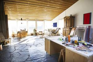 I det stora vardagsrummet, eller ateljén, vetter de stora fönstren mot söder. Från de stora skifferplattorna på golvet strömmar värmen och håller temperaturen i rummet.