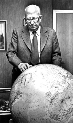Clas Ohlson vid en jordglob, en symbolisk bild eftersom det företag han startade idag är globalt.