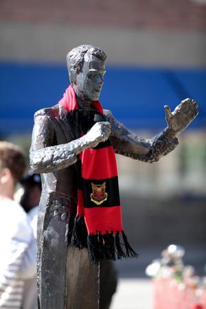 Snygg skulptur blir ännu snyggare så här, tycker ÖFK:s spelare och pimpade körledaren på torget.
