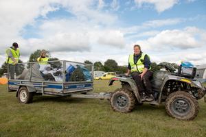 Maria Bergsten kör en av fyrhjulingarna. På släpvagnen, som de redan tömt tre gånger, står Elin Bergsten och Sebastian Holmgren.
