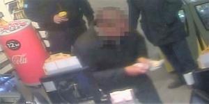 Bilden är från polisens förundersökning och visar hur 37-åringen (som har fått ansiktet maskat av LT) just fått pengar i handen. Han visste, sade han senare, att han skulle åka fast eftersom han uppträdde omaskerad.