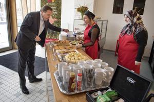 Statsminister Löfven fikar bland nyanlända i arbete.