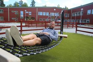 Allt är klappat och klart vid nya Viksbergskolan och rektor Jan Lindgren passar på att testa ett av skolgårdens lekredskap – en stabil hängmatta – innan allvaret sätter igång med upprop nästa onsdag.