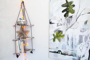 Ingelas hängande hörnhylla och konst med gröna blad.