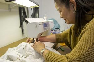 En jacka får ny dragkedja. Vid symaskinen sitter Somkit Khosnaw.