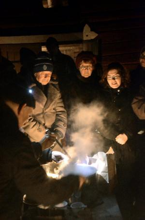 Eld och rök. Ångorna från buljongen blandar sig med röken från eldkorgarna i pausen mellan akterna på Stadra vinterscen. Närmast i bild Ingvar Lundqvist som serverar Elin Sörman.