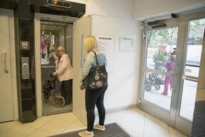 Nina Rantalainen håller upp dörren för sin mamma som försöker tråckla sig ur hissen med sin rullator.