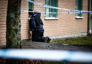 Kriminaltekniker säkrar bevis i form av en av de två kulor som träffade lägenhetens fönster.