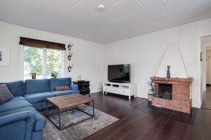 Vardagsrummet har fönster åt två håll, öppen spis och utgång till altanen.Foto: Länsförsäkringar Fastighetsförmedling.