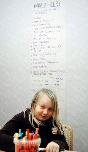 Linn Hjalmar ritar. På väggen bakom henne sitter de ungdomsgårdens regler, vilka alla tillsammans hjälp till att ta fram.