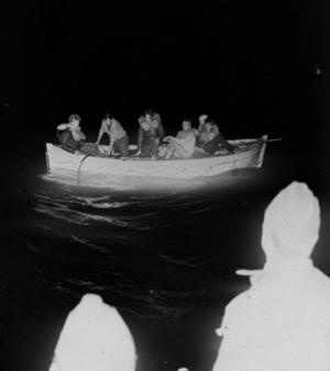 Ralf sitter i aktern i livbåten med en vit mössa på huvudet.