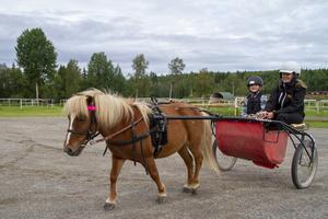 Glada miner när Hagmyrens Travskola arrangerade prova-på dag. I vagnen syns Liv Gabrielsson och skötaren Wilma Herranen.