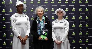 Margaret Atwood bär grönt på presskonferensen i London och omges av två kvinnor i fotsida klänningar – dock inte i rött som i tv-serien