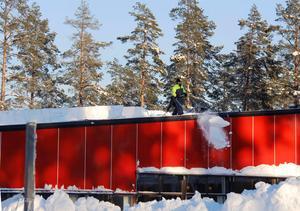 Metertjocka lager av snö rensas från Timrå gymnasiums tak.