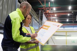 Christian Nilsson undertecknar checken som bekräftar att 20 000 kronor skänks till stiftelsen Nyckelfonden. Annika Rosdahl från Nyckelfonden tar emot.