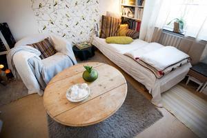 Mys- och läsrum med fågeltextil på väggen och bord med avsågade ben.