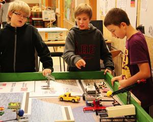 Emil Westum, Herman Häggström och Martin Johansson kontrollerar hur legoroboten fungerar.