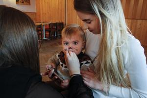 Matteus Fräki satt i knät på mamma Agne Jasinskaite medan han fick en ansiktsmålning av Emma-Marie Hisved.