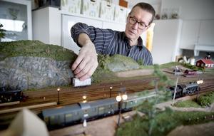 Arne utgår från kartor och ritningar när han bygger sin modell. Vagnarna och loken är tidstypiska för 1914.