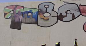Städare vid en mur där man målat årtionden och vad Mandela uppnådde under den tiden.