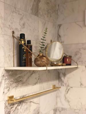 Det nyrenoverade badrummet går i guld och marmor.