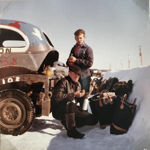 Olle Nielsen sitter och tar en fika. Bakom står framlidne Sören Svalking, bilplåtslagare från Östersund. Olle Nielsen tror bilden kan vara tagen i Östersund, omkring 1958.
