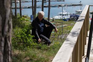 Lars Pousette bredvid den sällsynta fältsippan som Länsstyrelsen menar hotas av det byggda serveringsdäcket.