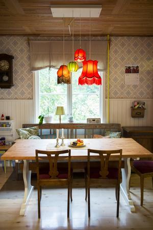 Lamporna ovanför matbordet ger en mysig känsla till matplatsen.