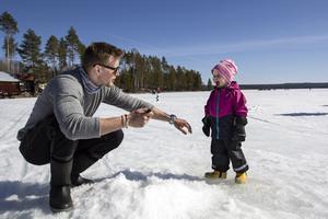 Kristian Domander och dottern Wilma 2,5 som tyckte det var skoj att sparka ned issörja i pimpelhålet.