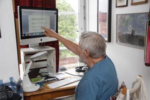 """Vid datorn skriver Bosse Kärvinge ner sin lek med ord, här homofoner i ramsan """"låt dem gärna tvätta din hjärna i Järna""""."""