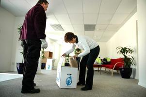 Det är många lådor att hålla ordning på när ett helt kontor ska flyttas. Anne Resare kontrollerar innehållet i en omärkt låda för att se var Rainer Yli-Tokola ska bära den.