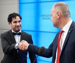 Civilminister Ardalan Shekarabi (S) har tagit partiledaren Jonas Sjöstedt (V) i hand på att lägga fram förslaget på ett vinsttak i välfärden till riksdagen. Foto: Anders Wiklund/TT