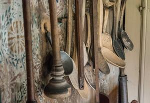 I köket. Överallt finns föremål som lämnades kvar på hyllor och krokar – bestick, husgeråd, mattor och andra textilier.