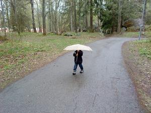 Jonathan, då 2,5 år, är ute och går i regnet och skulle absolut hålla paraplyet själv.