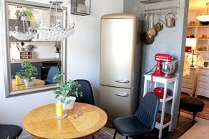 Kylskåp i guld, loppisbord och moderna stolar med mjuk sits.