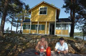 Krister Modd och Lars Engelbrektsson dricker en kopp kaffe i skuggan av tallarna.