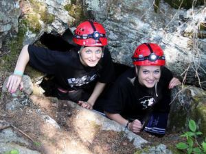 Elin Sundberg och Linnea Ögren på väg ner i en av de elva grottorna som finns på Midskogsberget.