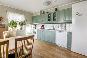 Köksinredningen har en mild pastellfärg och här finns även plats för bord och stolar.Foto: Fastighetsbyrån.